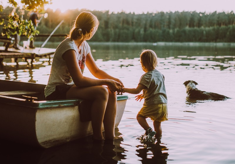 Frau mit Kind sitzen am See und schauen auf ihren Hund im Wasser