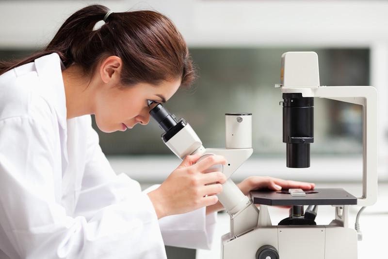 Frau mit Kittel schaut ins Mikroskop im Labor