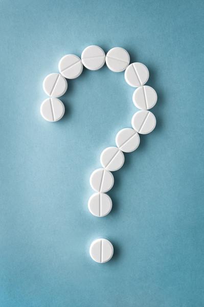 Fragezeichen gelegt aus weißen Tabletten vor blauer Unterlage